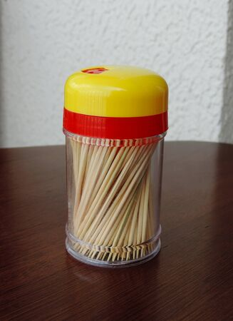 A toothpick container on the wooden table Imagens