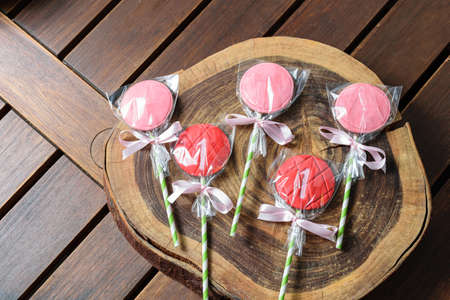 Strawberry flavored chocolate lollipops on a wooden log board. Imagens