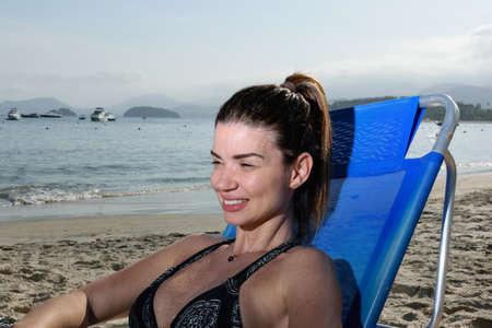 Mature woman sitting on a lounger on a Brazilian beach.
