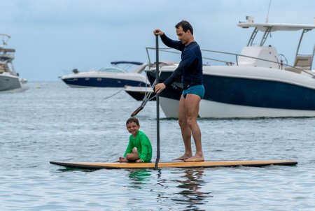 Father and son (smiling) with standup-paddle board.