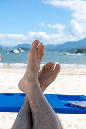 Man relaxing on the beach with his feet on a table.