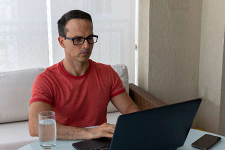 Mature man with glasses working at home (with cellphone and a glass of water at his side). 免版税图像