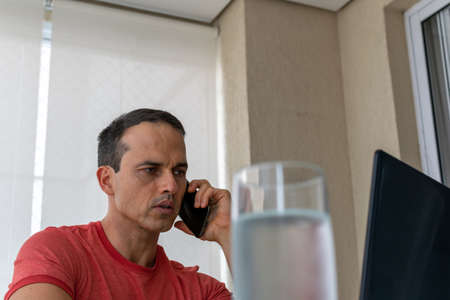 Mature man working at home and holding cellphone in hand, looking at the screen of his laptop (iced glass of water in the foreground).