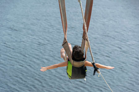6 year old child going down with the zip line in the Jacomã Lagoon in the city of Ceara-Mirim / RN-Brazil.