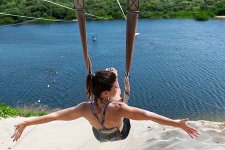 Woman sitting on her back and looking sideways on a zip line overlooking the Jacomã Lagoon in the city of Cera Mirim-RN / Brazil.
