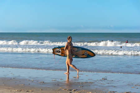 Natal, Ponta Negra Beach, Rio Grande do Norte, Brazil, on july 27, 2019: Surfer woman looking for the best place to surf at Ponta Negra beach. Editorial