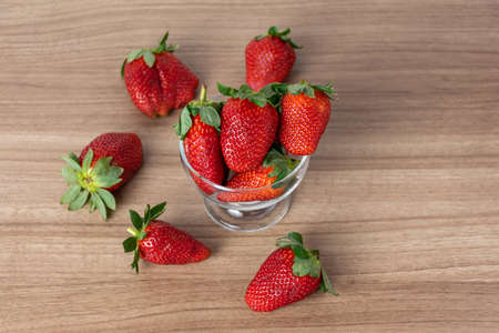 Strawberries scattered on wooden table background (top view). Imagens