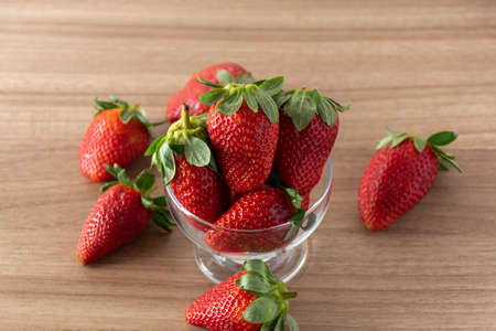Strawberries scattered on wooden table background. Imagens