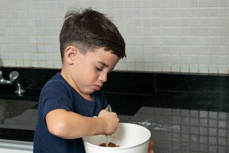Boy mixing cookie dough with a metal spoon_photo 2. 版權商用圖片