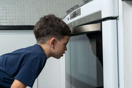 Boy checking on the stove if cookies are ready. 版權商用圖片