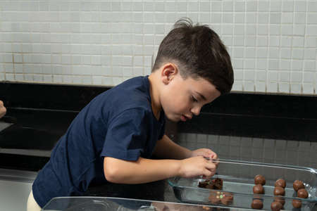 Boy putting the finishing touches on decorating cookies. 版權商用圖片