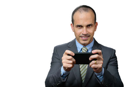 Mature man with suit and tie, smiling and holding smarthphone horizontally.
