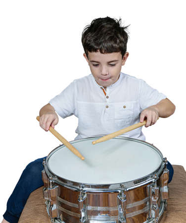 7 year old child concentrated and playing drums. White background.