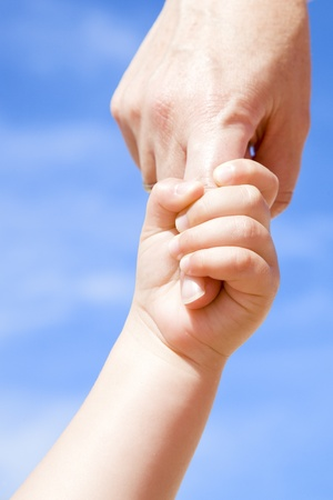 Adult holding a child by the hand against a cloudy blue sky photo