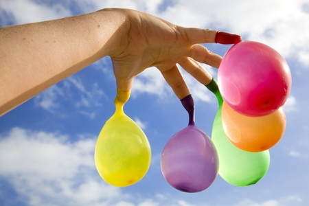 Open hand with multicolored water filled balloons hanging from the fingers, with a cloudy blue sky as background