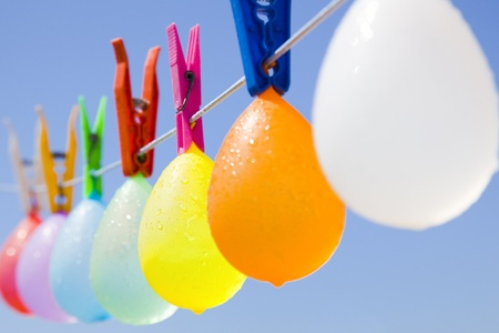 Selective focus on a colored bunch of balloons with waterdrops hanging on a clothesline with a blue sky as background Standard-Bild