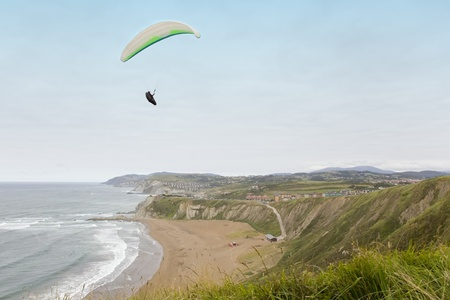 Paraglider flying over a beach near the seashore photo