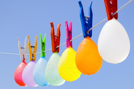 Selective focus on a colored bunch of balloons with waterdrops hanging on a clothesline with a blue sky as background Zdjęcie Seryjne