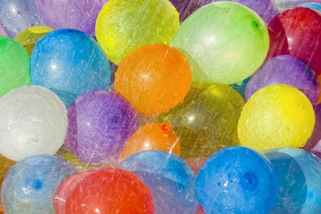 Water drops falling over multicolored water filled balloons photo