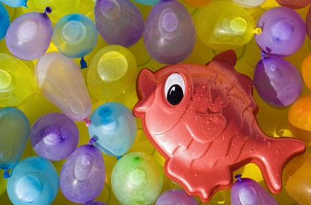 Red toy fish swimming between colored ballons photo