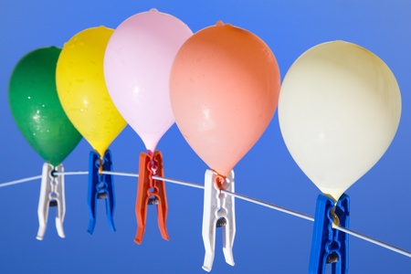 rise to the top: Group of colored water filled balloons with waterdrops hanging on a clothesline with a blue sky as background,  seen from above Stock Photo