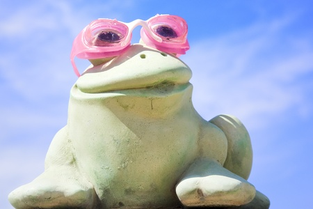 stimulate: Green frog statue with pink swimming glasses against a cloudy blue sky