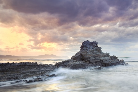 Seascape showing waves breaking against a rock on the coast with a cloudy stormy sky and the sun appearing in the background Stock Photo - 13499391