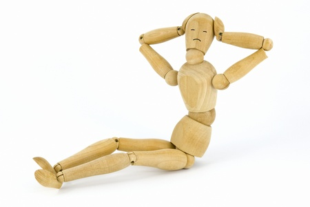 Sitting wooden toy man on a white background as a concept of press-ups, with copy-space Standard-Bild