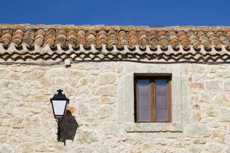 lamp made of stone: Facade made of stone, window and lamp in a rustic house