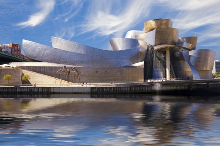 Guggenheim Bilbao museum reflection on the Nervion river, over a cloudy blue sky