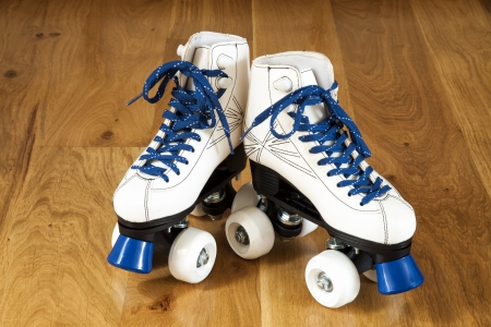 Pair of roller skates on a wooden background