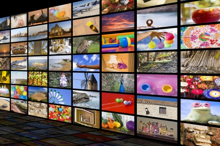 Big TV videowall with different channels in a black room with reflection