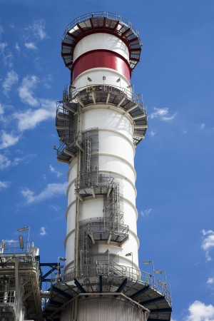 electric utility: Close view of the stack of a power plant against a cloudy blue sky Stock Photo