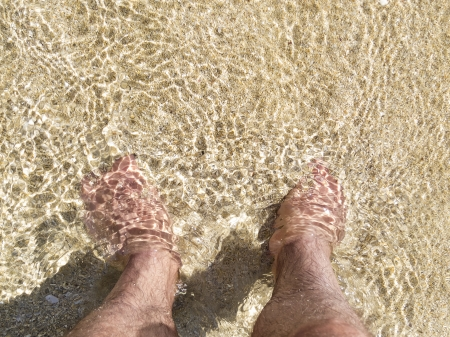 bodypart: Feet in the sand in shallow water with copy space