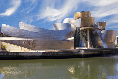 Guggenheim Bilbao museum reflection on the Nervion river, over a cludy blue sky Publikacyjne