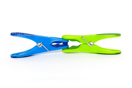 aggresive: Green clothespin clamping blue clothespin on a white background