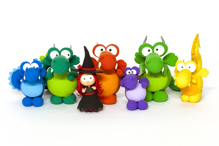 clay modeling: Multicolored handmade modelling clay dragons and red haised young witch on white