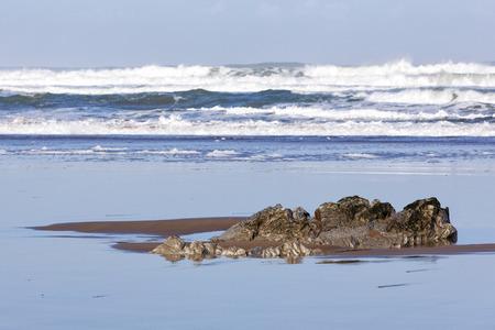 mare agitato: Messa a fuoco selettiva in una roccia sulla spiaggia contro un mare agitato