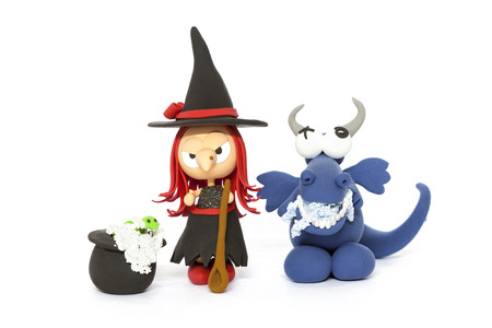 clay modeling: Handmade modelling clay red haired witch and blue dragon on white