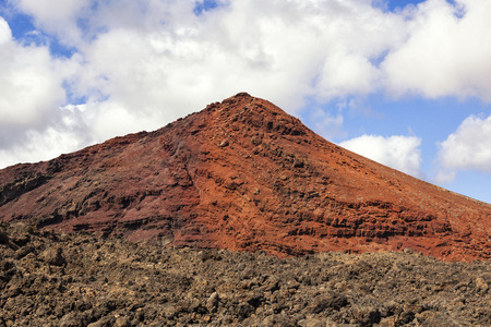 solidified: Red volcano with solidified lava in the foreground in Lanzarote, Canary islands, Spain