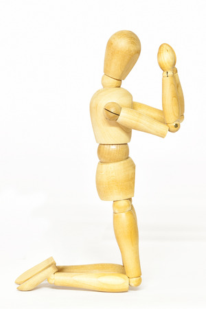 pleading: Conceptual representation of praying with wooden mannequin