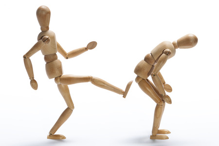 Wooden mannequin kicking in the backside to other as a concept of fired