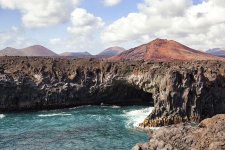 los hervideros: Los Hervideros, shoreline cave in Lanzarote, Canary Islands, Spain, with volcano