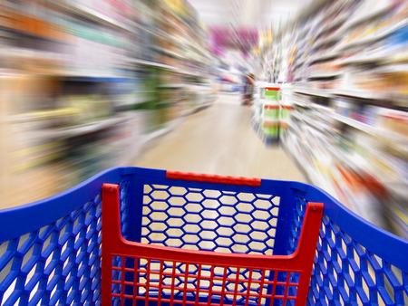 gente corriendo: Carro sobre un fondo borroso en un supermercado como un concepto de compra rápida