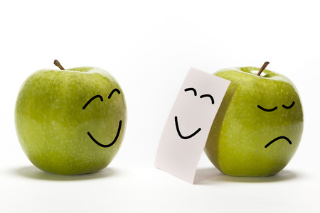 caras tristes: Una sonrisa de la manzana a otra que está ocultando su tristeza detrás de una máscara sonriente Foto de archivo