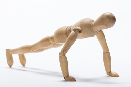 pushup: Wooden mannequin doing push-up exercise Stock Photo