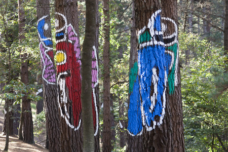 oma: Motorcyclists painted on trunks in the Oma forest, by Agustin Ibarrola, in the Basque Country, Spain Stock Photo