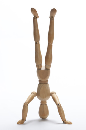 handstand: Wooden mannequin doing a handstand on a white background