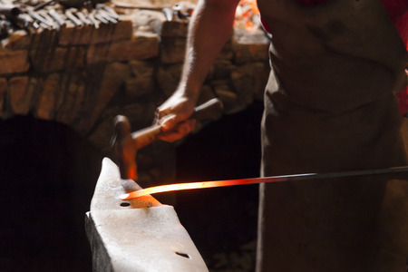 Blacksmith forging steel with hammer and anvil for hammering blurred sense of motion