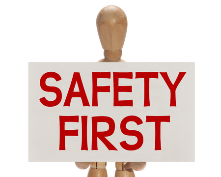 cautionary: Wooden mannequin holding a white card with the message Safety first over a white background Stock Photo